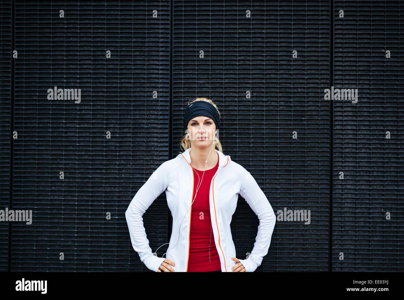 Ritratto di giovane attraente donna che guarda fiducioso nell'abbigliamento sportivo. Femminile all'esterno. Immagini Stock