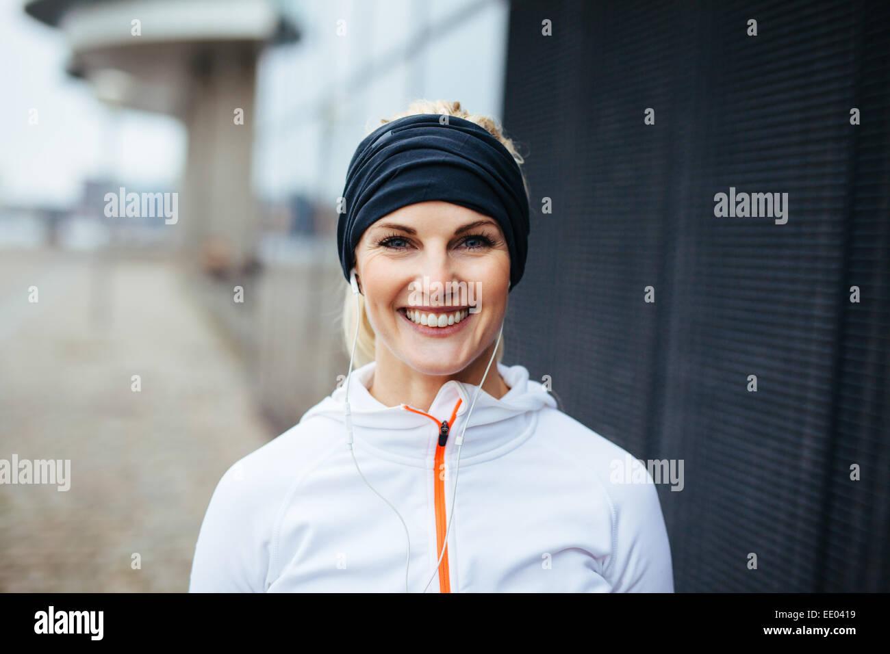 Ritratto di Allegro giovane donna fitness. Sorridente giovane atleta femminile in sports wear all'esterno. Immagini Stock