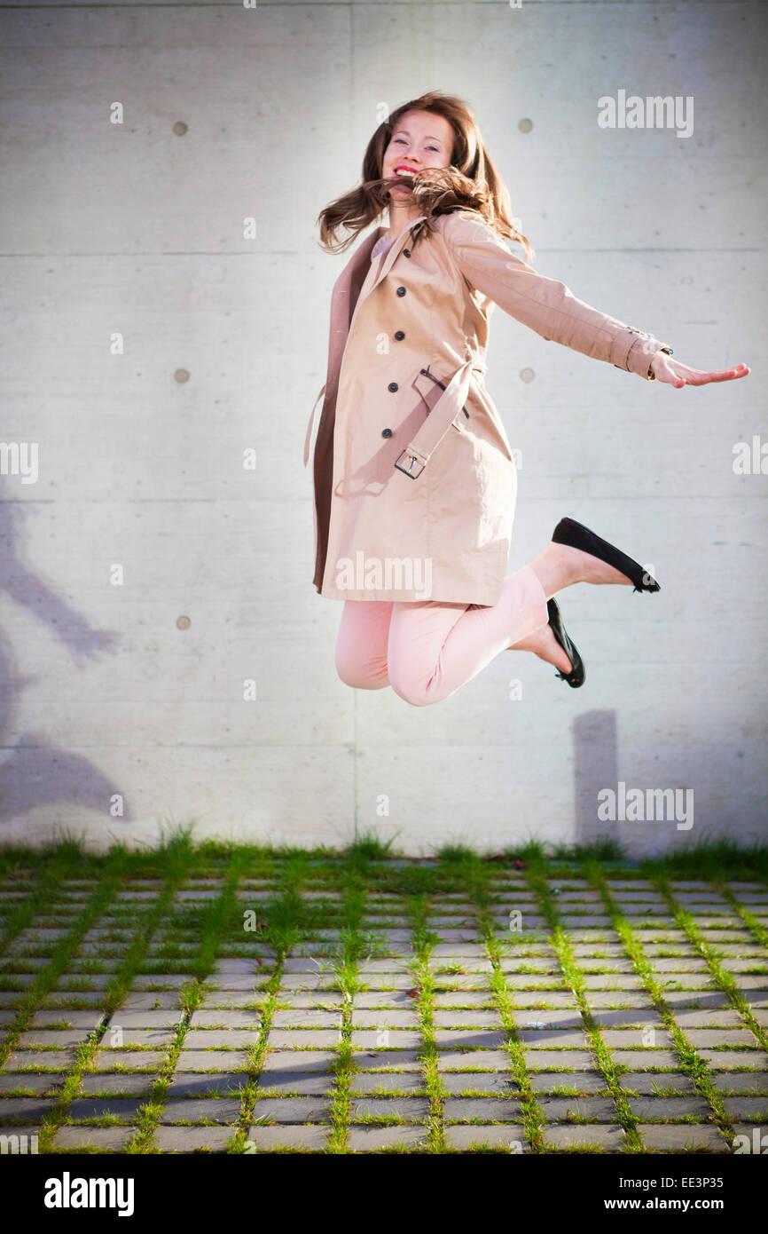 Giovane donna salta all'aperto, Monaco di Baviera, Germania Immagini Stock
