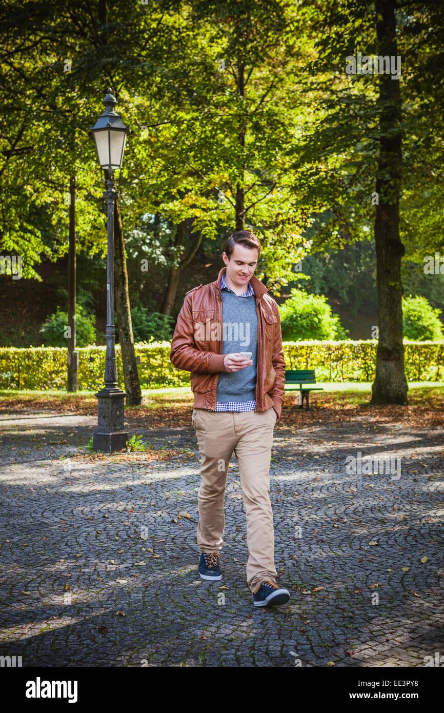 Giovane uomo di messaggistica di testo all'aperto, Monaco di Baviera, Germania Immagini Stock