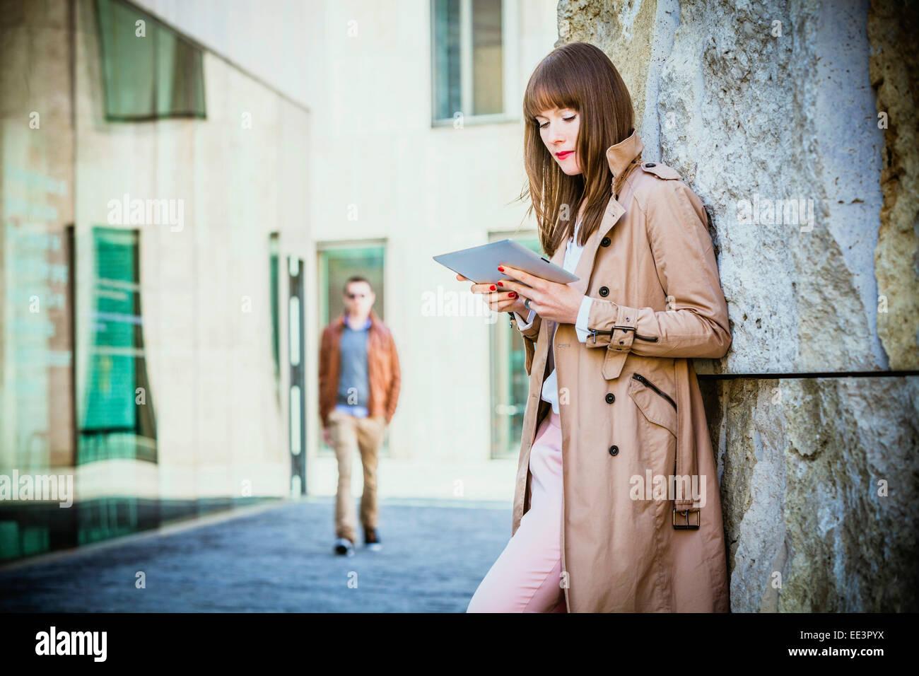 Giovane donna con tavoletta digitale all'aperto, Monaco di Baviera, Germania Immagini Stock