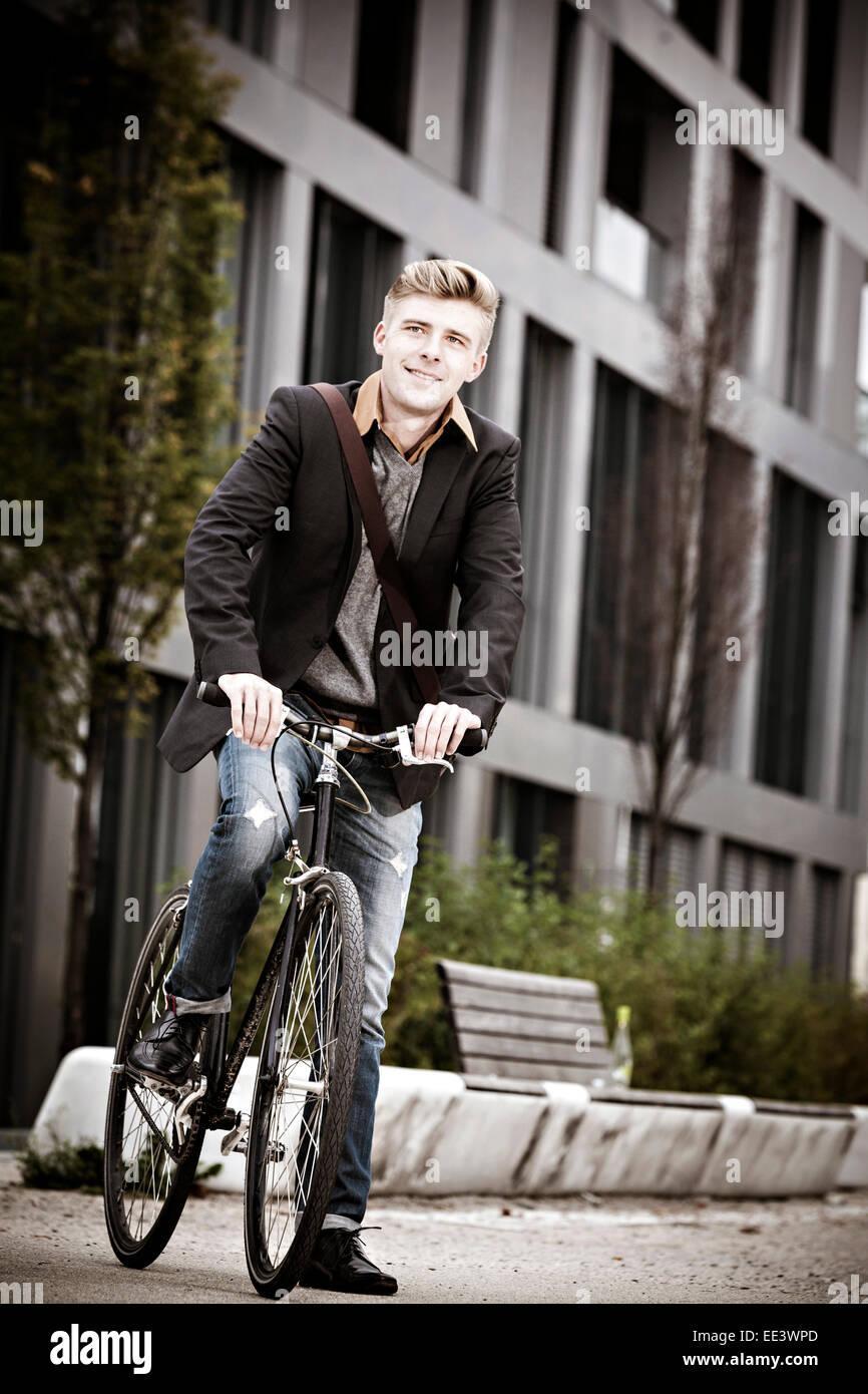 Giovane imprenditore con bicicletta sulla via della città di Monaco di Baviera, Germania Immagini Stock