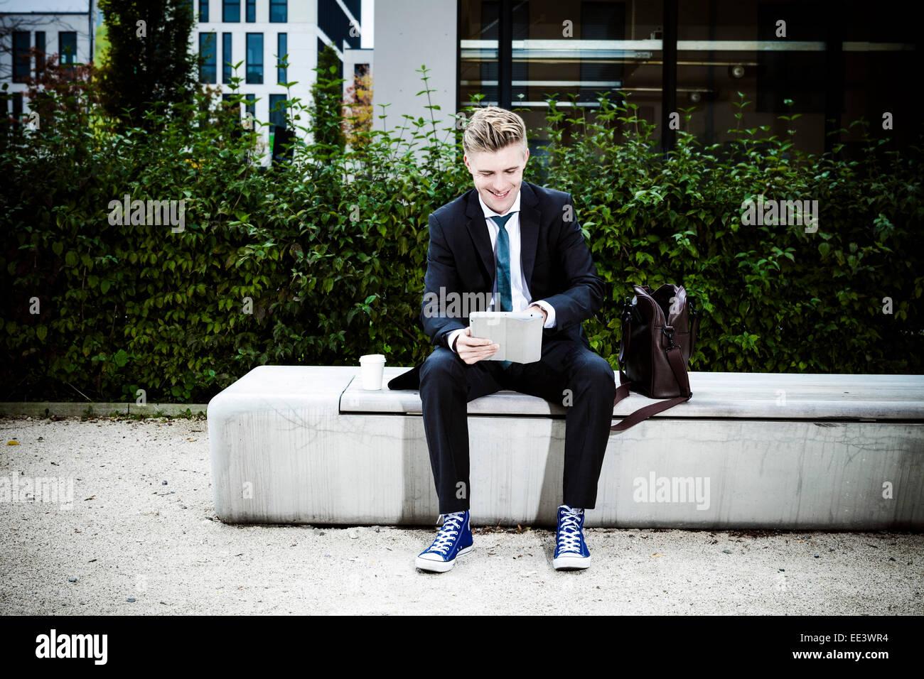 Giovane impreditore con tavoletta digitale all'aperto, Monaco di Baviera, Germania Immagini Stock