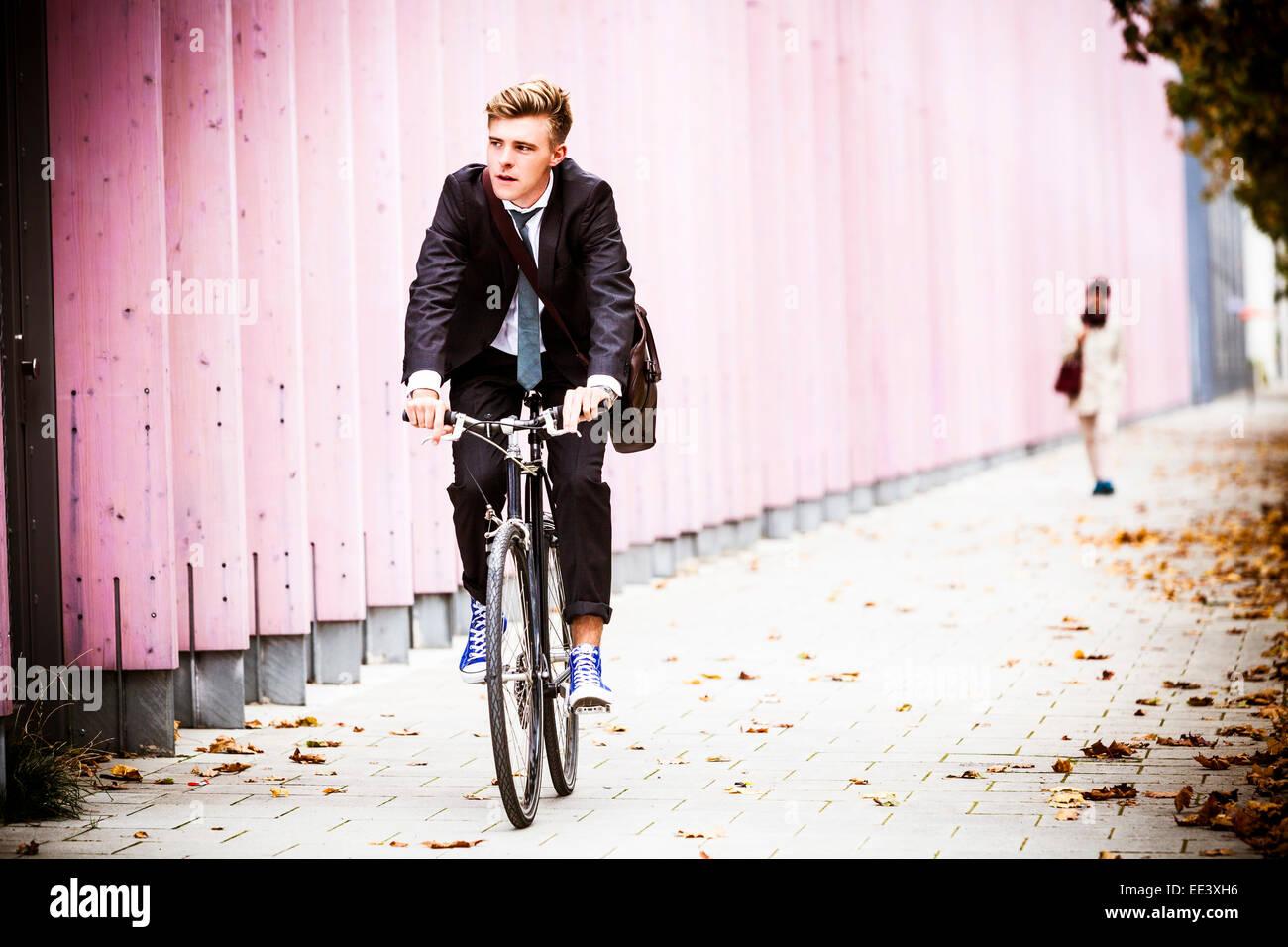 Giovane imprenditore Bicicletta Equitazione, Monaco di Baviera, Germania Immagini Stock