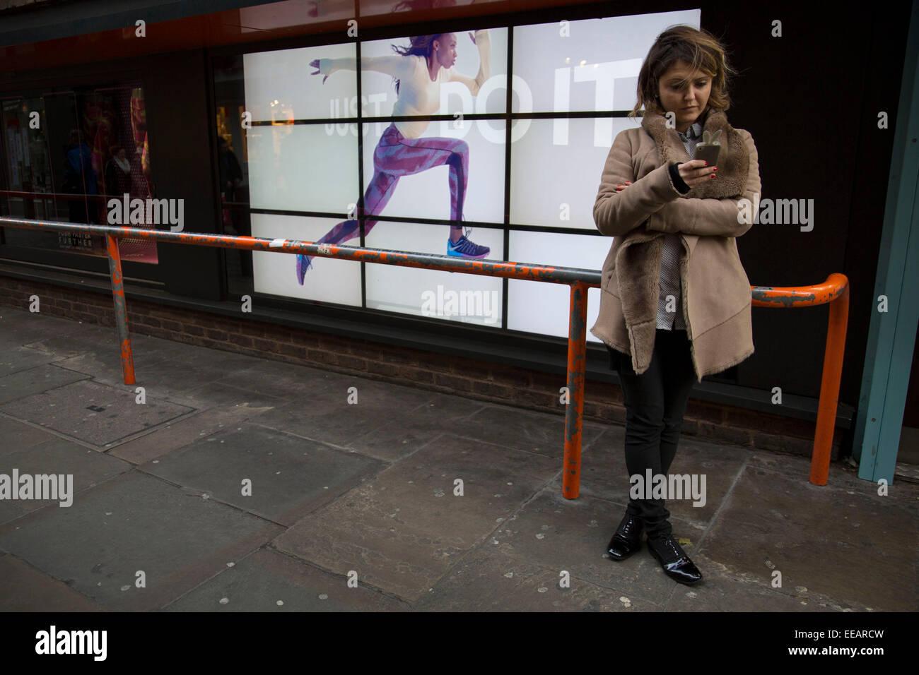 Pubblicità Nike runner corre lungo una barriera vicino gli ignari cittadini. Il video annuncio pubblicitario Immagini Stock