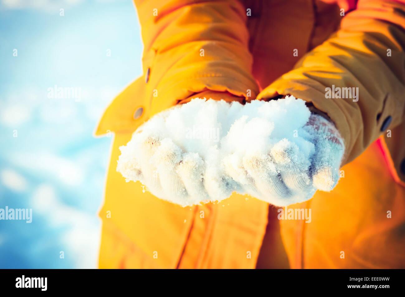 Neve nelle mani della donna dando inverno vacanze in uno stile di vita all'aperto Immagini Stock