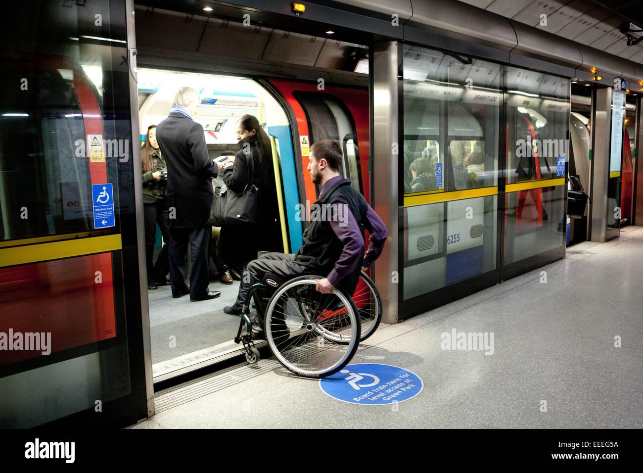 Utente di sedie a rotelle di salire a bordo della metropolitana di Londra in treno Immagini Stock