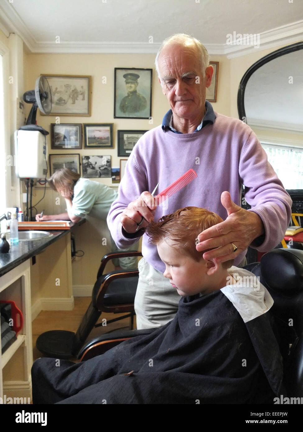Un barbiere il taglio di un ragazzi capelli Immagini Stock