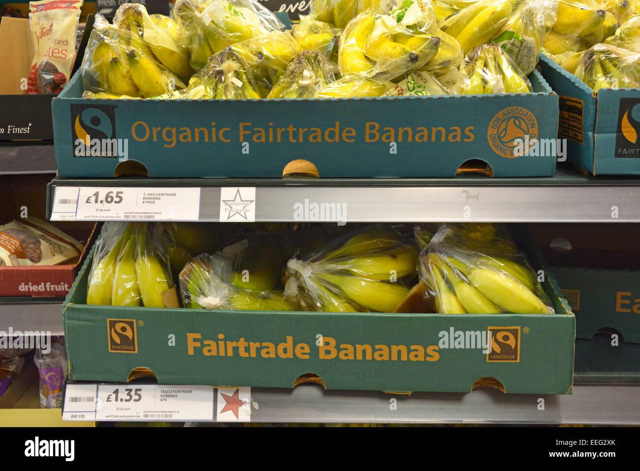 Borse di commercio equo e solidale e di banane biologiche nelle caselle visualizzate sugli scaffali per la vendita Immagini Stock