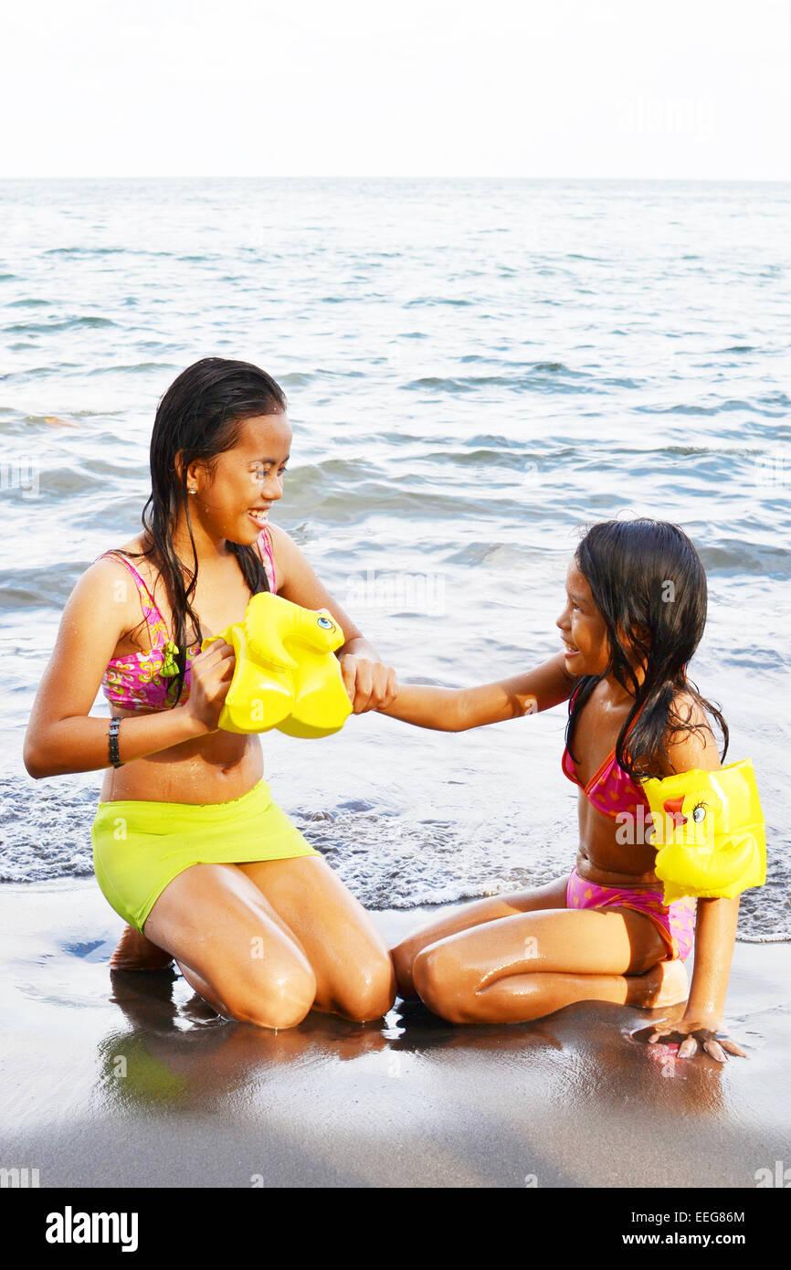 Teen girl aiutando la sua sorella più giovane ad usura fascia braccio di sicurezza dell'acqua Immagini Stock