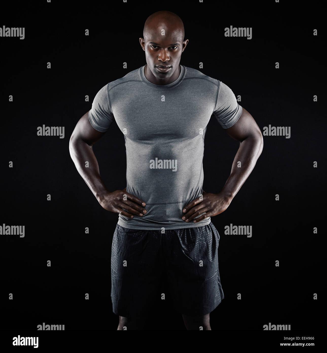 Ritratto di giovane muscolare uomo abbigliamento sportivo in piedi con le mani sui fianchi su sfondo nero. Forte Immagini Stock