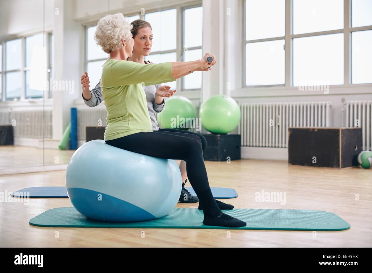 Trainer femmina assistere senior donna sollevamento pesi nella palestra. Senior donna seduta sulla sfera di pilates Immagini Stock