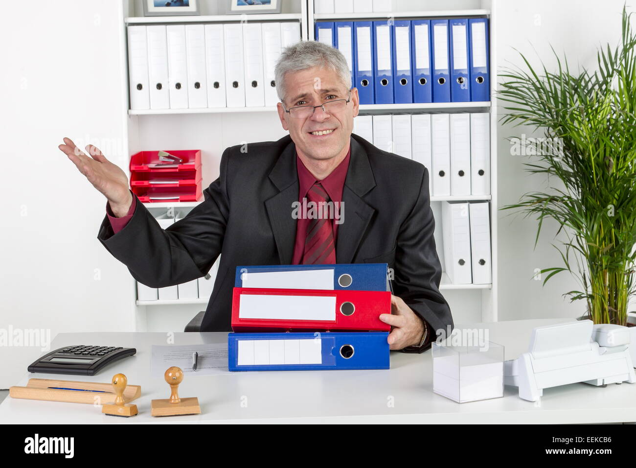 Mann mittleren altera sitzt im Büro und gestikuliert, uomo di mezza età, seduto nel suo ufficio, gesticulating Foto Stock