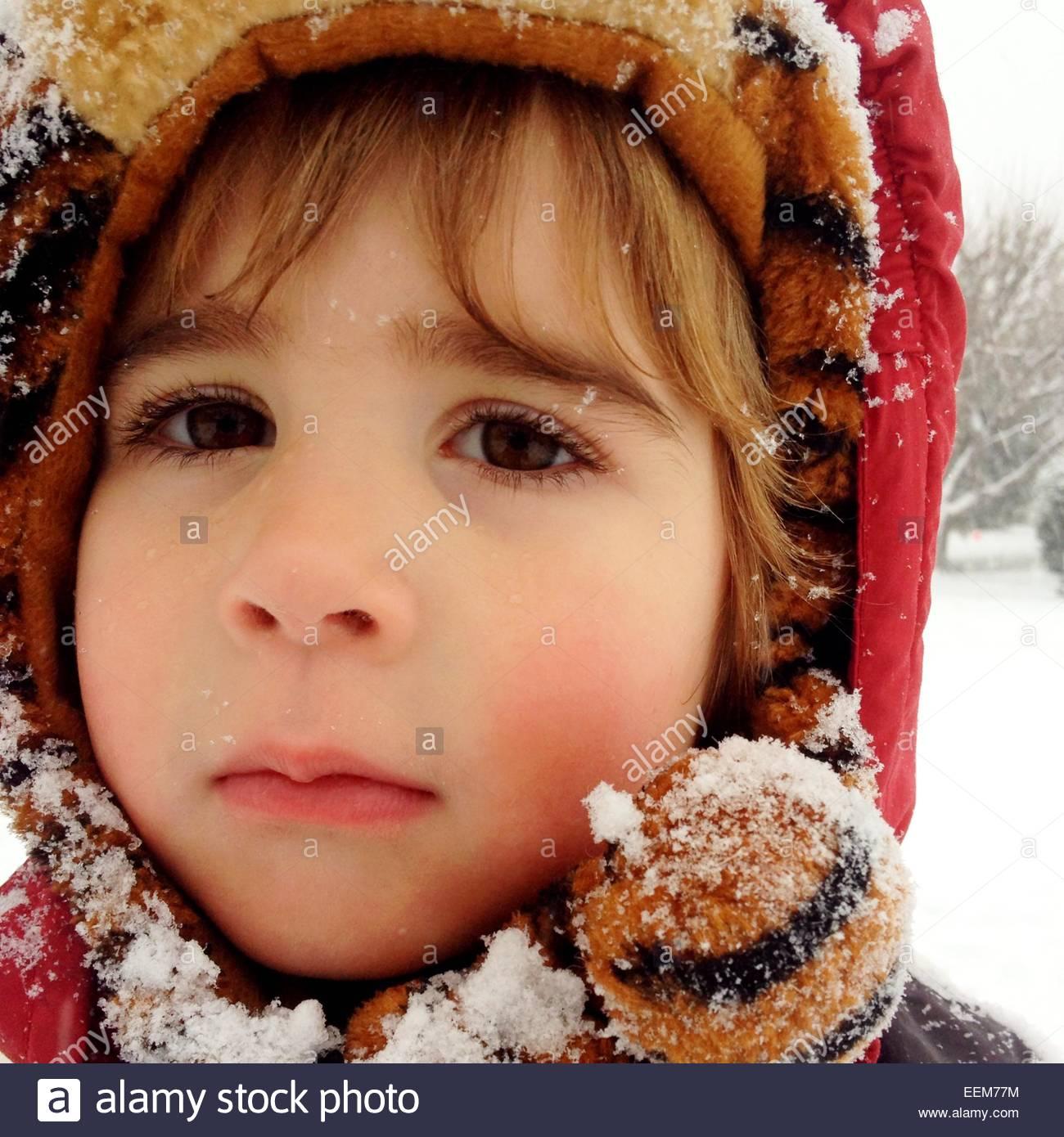 Colpo di testa di un ragazzo che indossa incappucciati abbigliamento invernale cosparsi di neve Immagini Stock