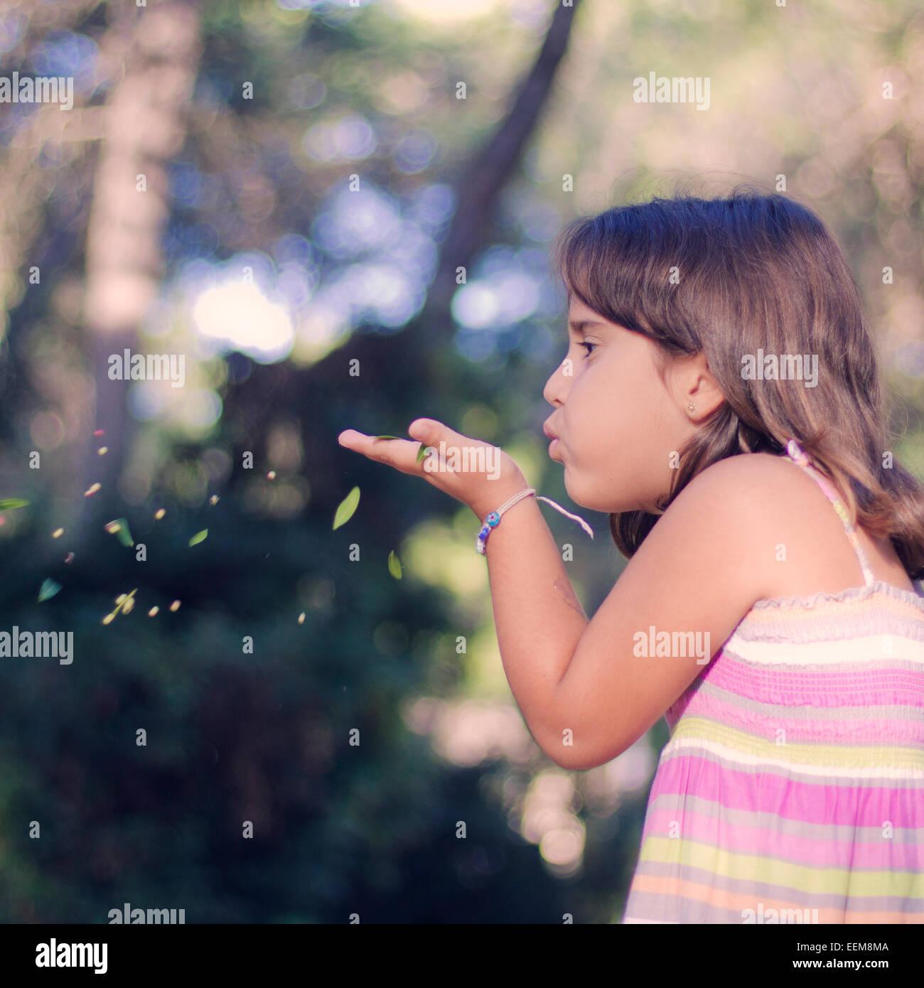 La ragazza (6-7) foglie di soffiatura di mano Immagini Stock