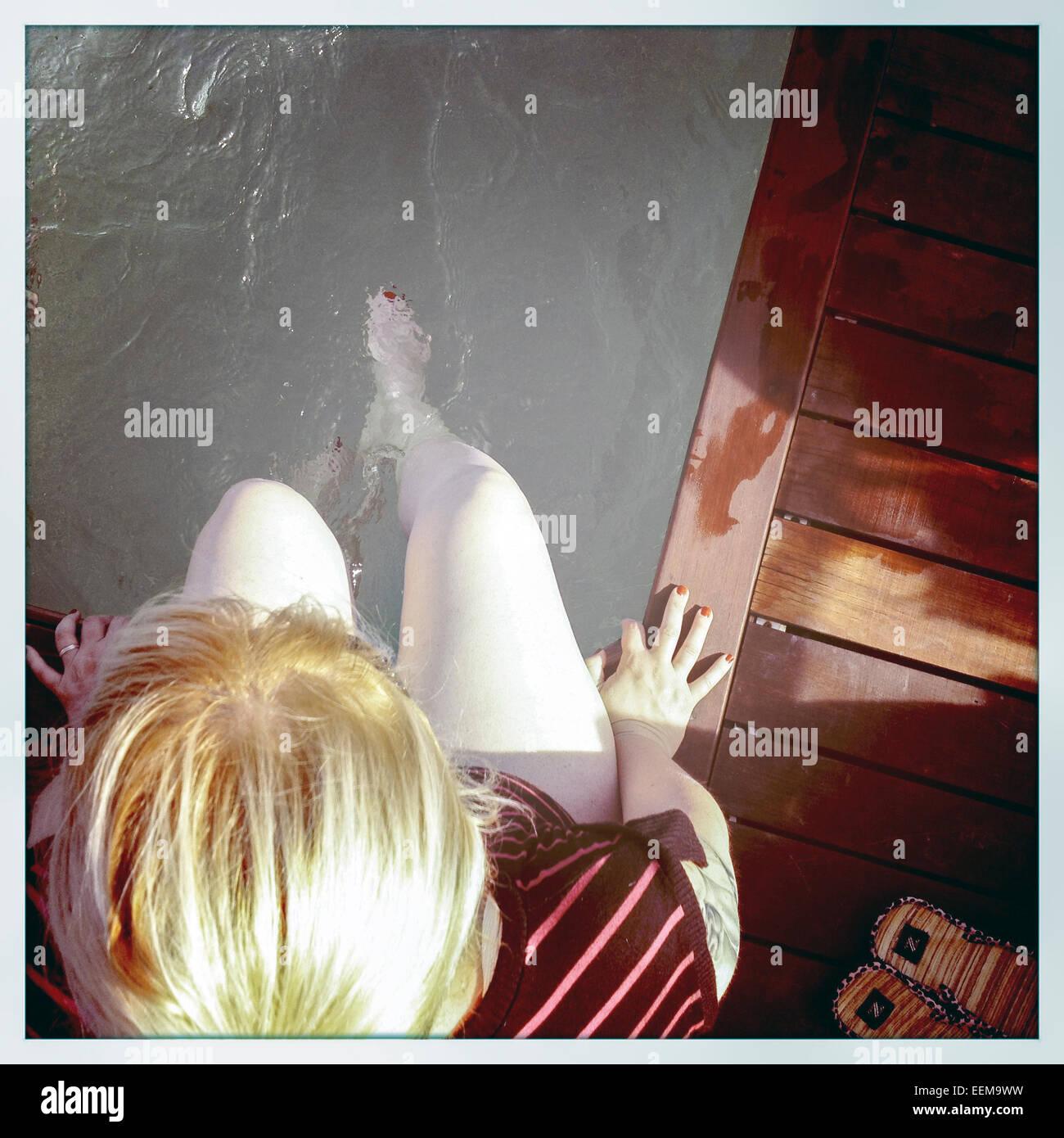 Elevato angolo di visione della donna seduta al bordo della piscina Immagini Stock