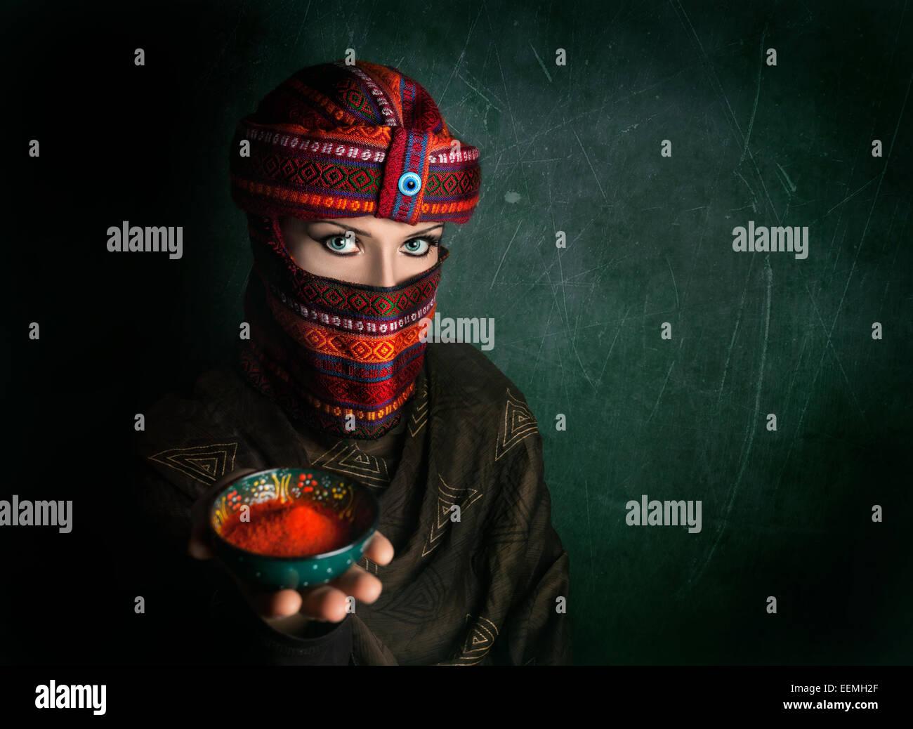 Donna orientale in turbante offrendo il peperoncino rosso in polvere in verde parete testurizzata Immagini Stock