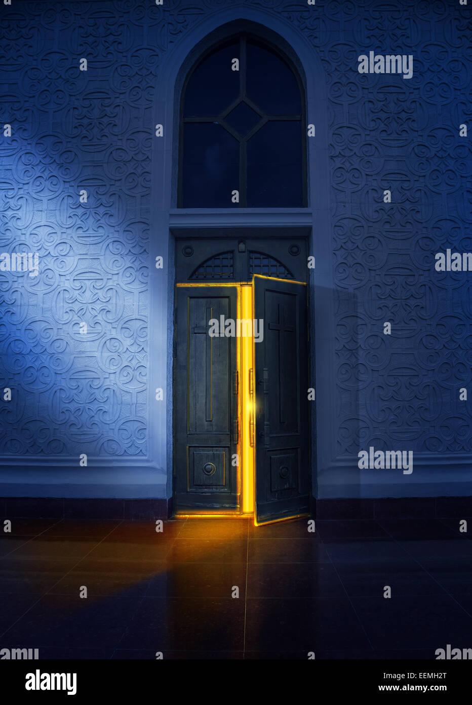 Apertura della porta con il bagliore giallo nella chiesa di notte Immagini Stock
