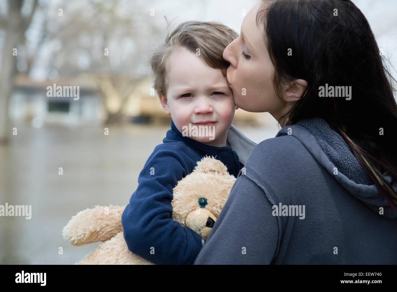 Madre e figlio in piedi in città allagate Immagini Stock