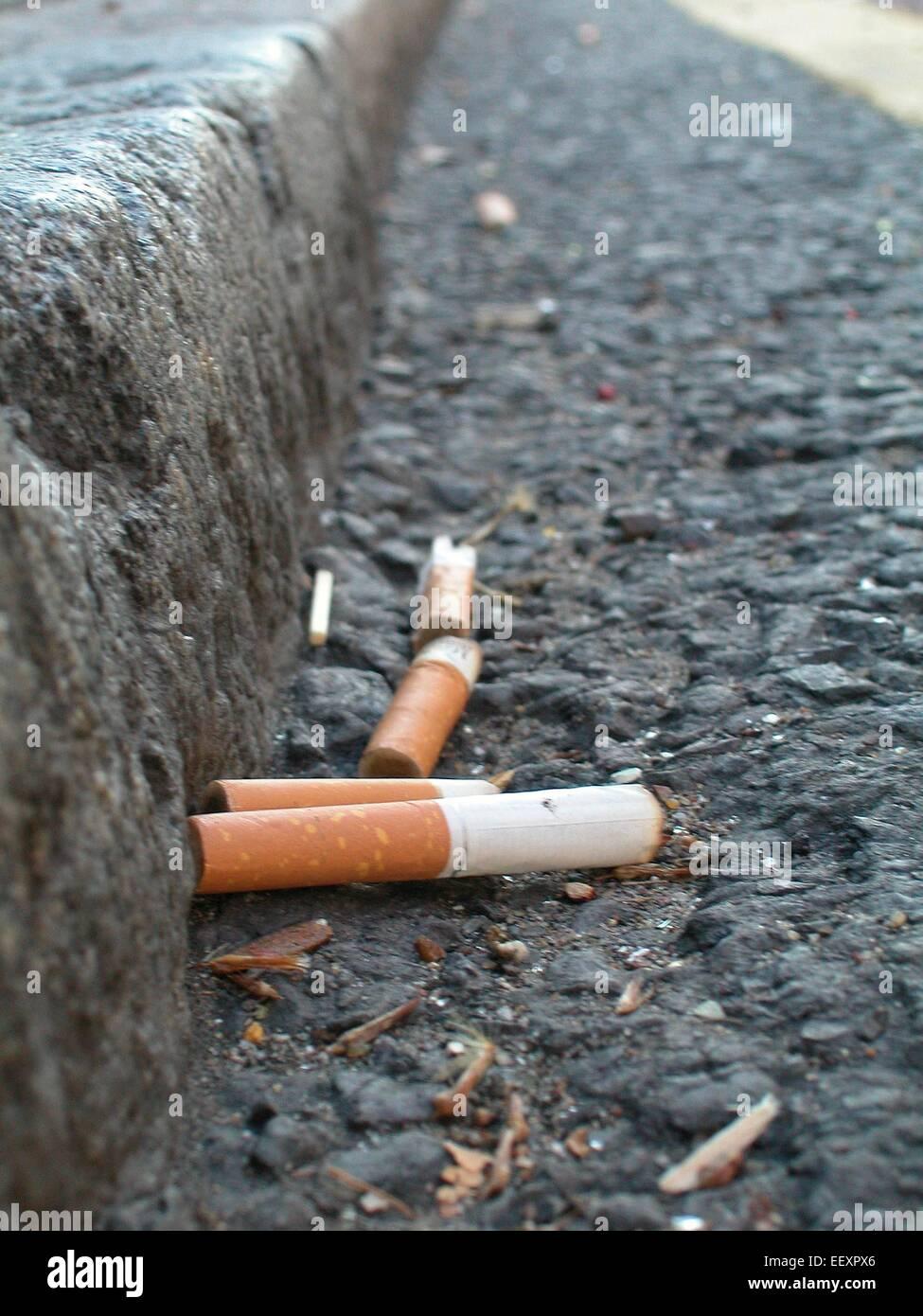 Sigaretta mozziconi di sigarette nella grondaia scartato materiale da fumo di lettiera problemi di salute Immagini Stock