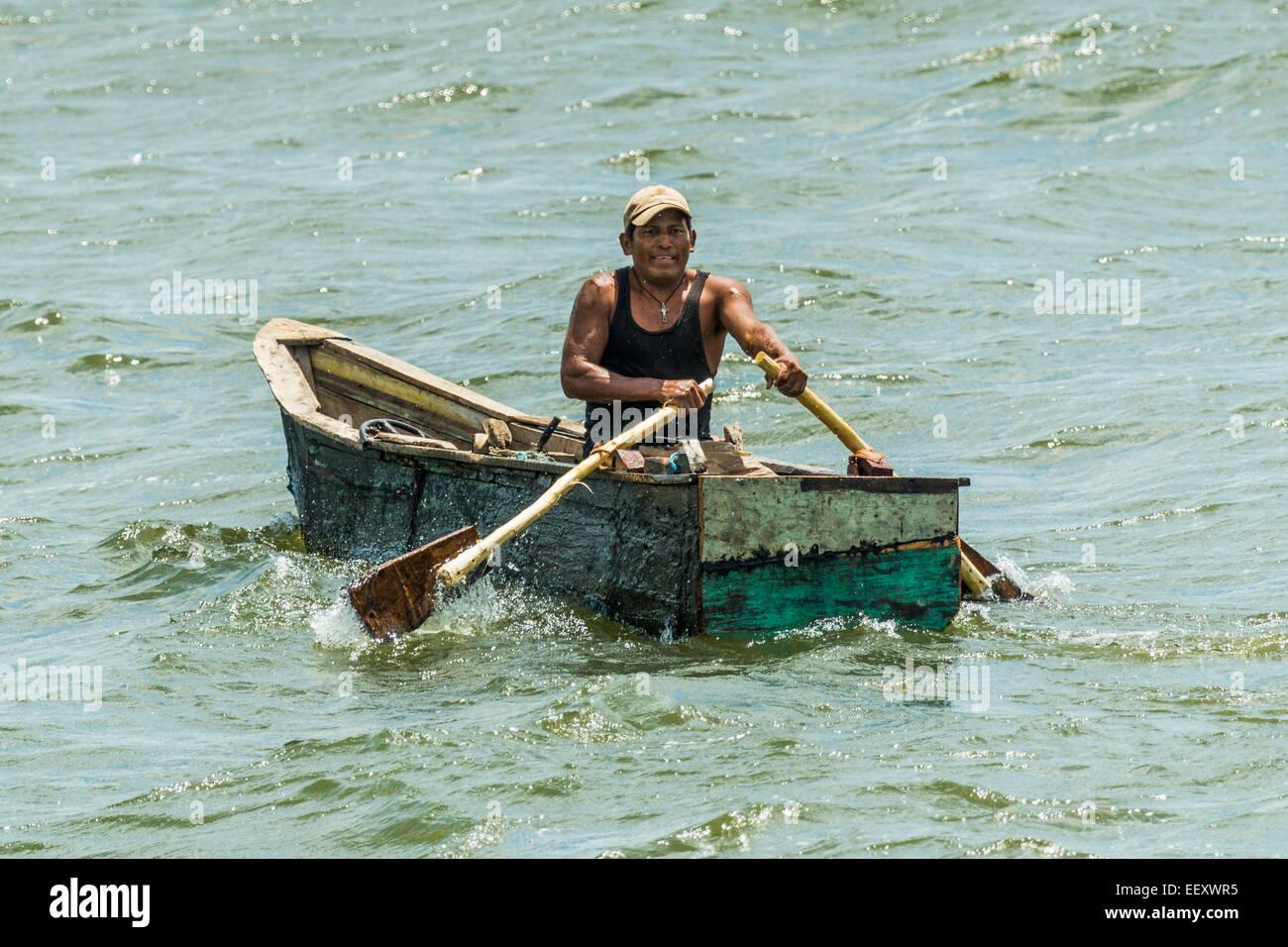 Uomo di canottaggio in casa piccola barca offshore del Myogalpa e popolare isola Omotepe; Isla Omotepe, Lago di Immagini Stock