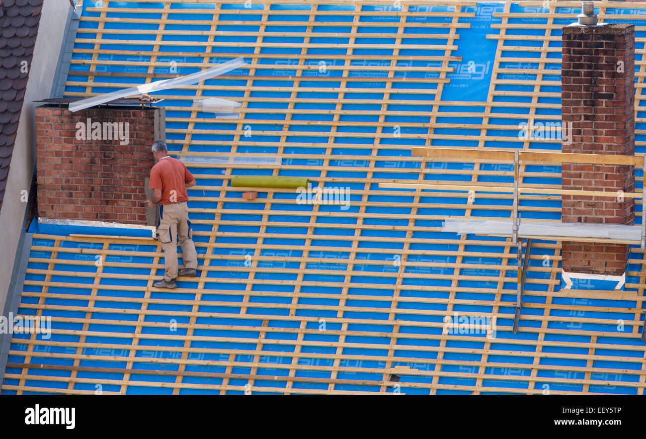 Builder su un ripido tetto su edificio senza alcuna attrezzatura di sicurezza Immagini Stock