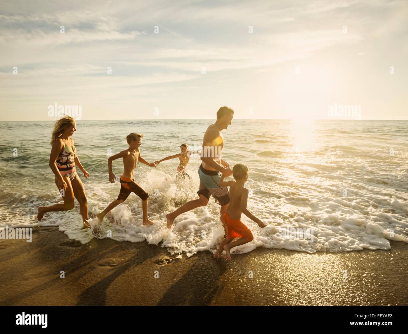 Stati Uniti, California, Laguna Beach, la famiglia con tre bambini (6-7, 10-11, 14-15) in esecuzione sulla spiaggia Immagini Stock