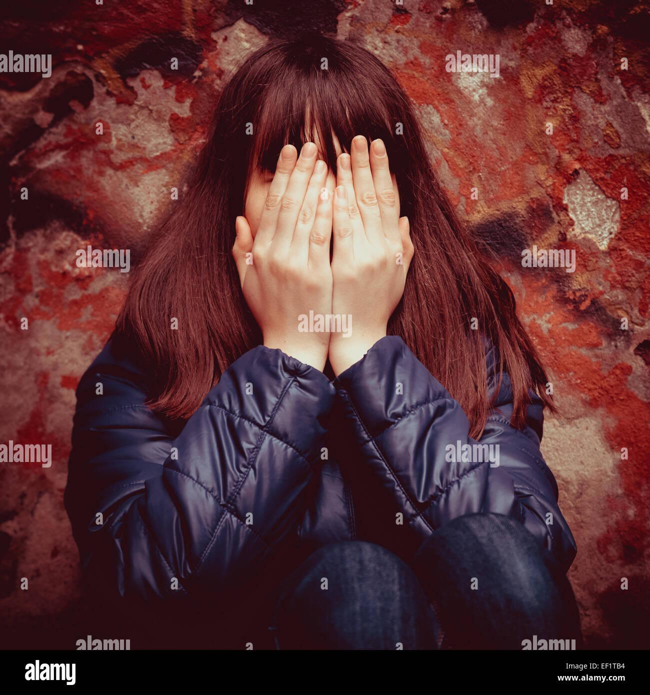Ragazza adolescente con le mani sopra gli occhi vicino drammatica parete rossa all'aperto Immagini Stock