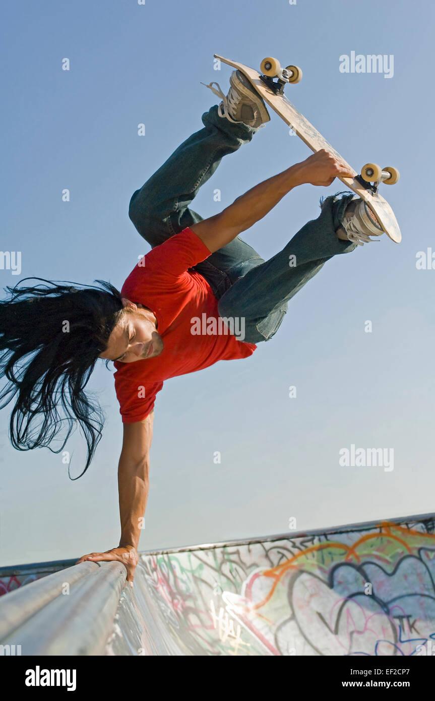 Un giovane uomo lo skateboard su una rampa da skateboard Immagini Stock