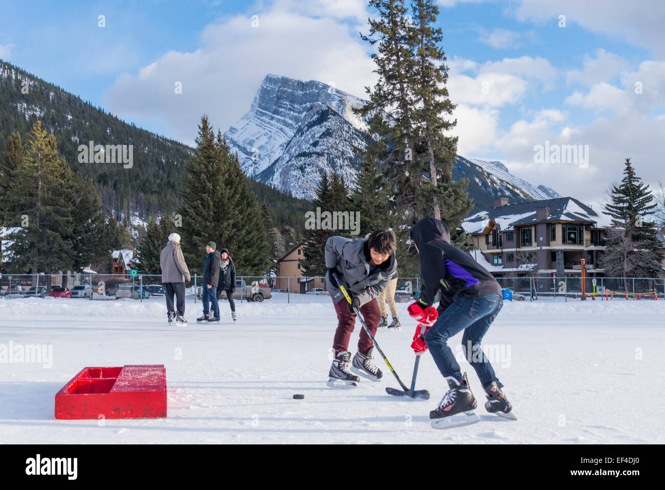 Ragazzi che giocano a hockey su ghiaccio, Banff, il Parco Nazionale di Banff, Alberta, Canada Immagini Stock