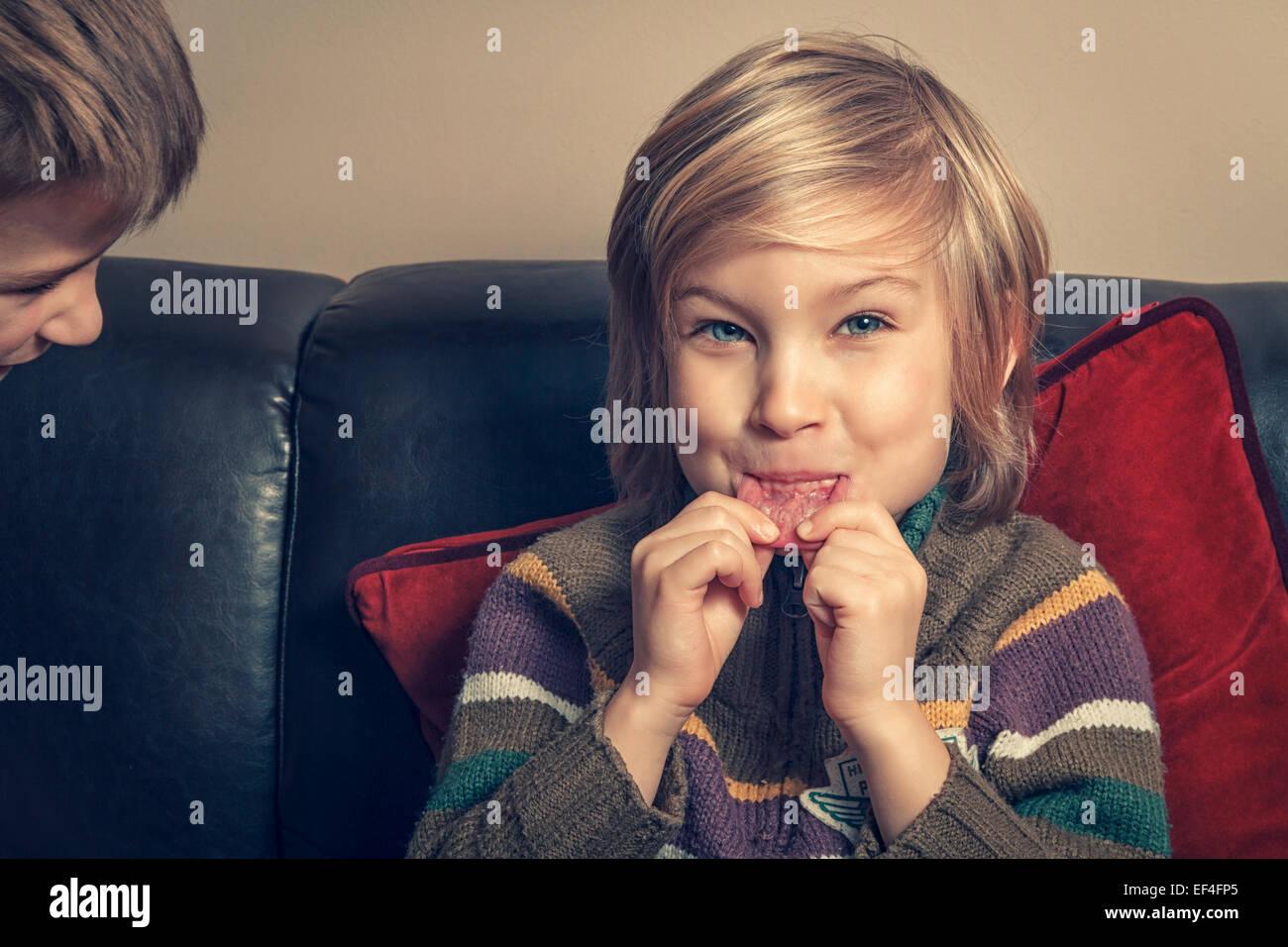 Giovane ragazzo in soggiorno facendo una faccia. Immagini Stock