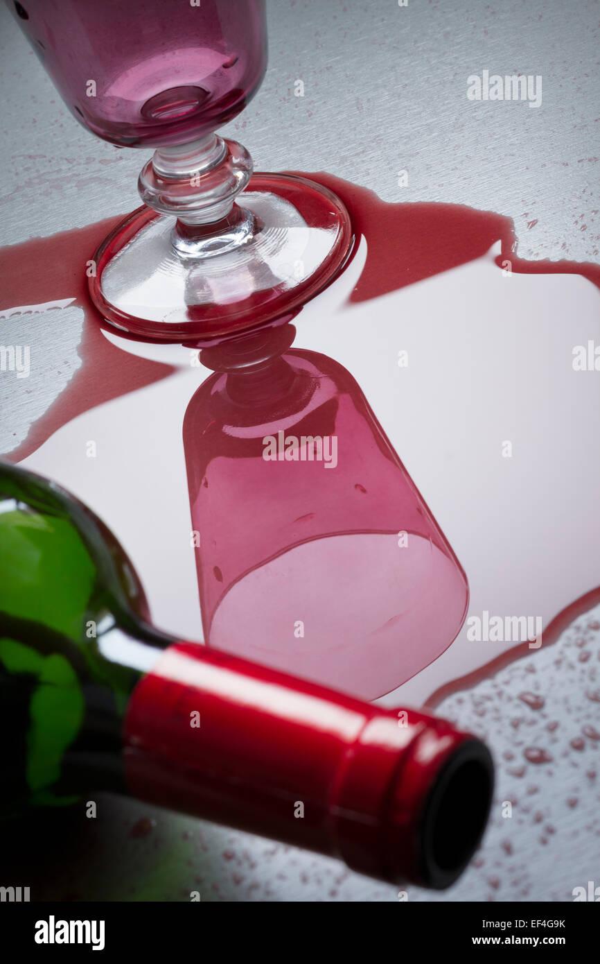 Bottiglia di vino rovesciato sopra accanto al vetro. Immagini Stock