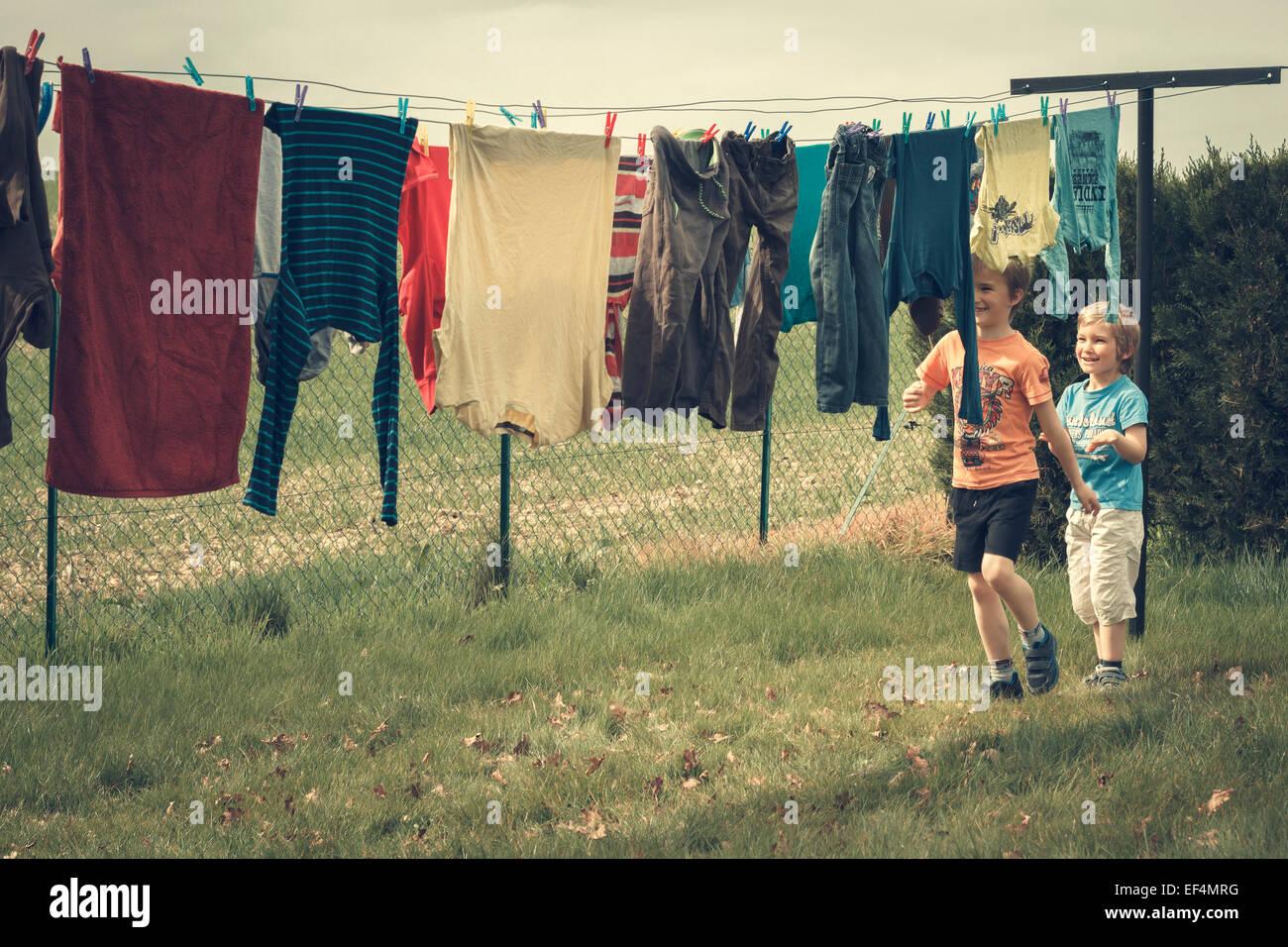 Fratelli giocare all'aperto Servizio lavanderia appeso Immagini Stock