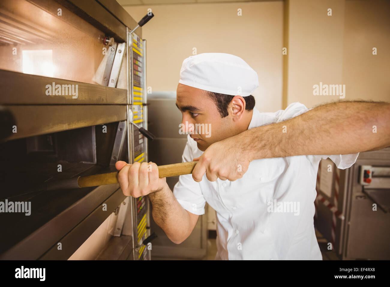 Baker prendendo il pane al di fuori del forno Immagini Stock