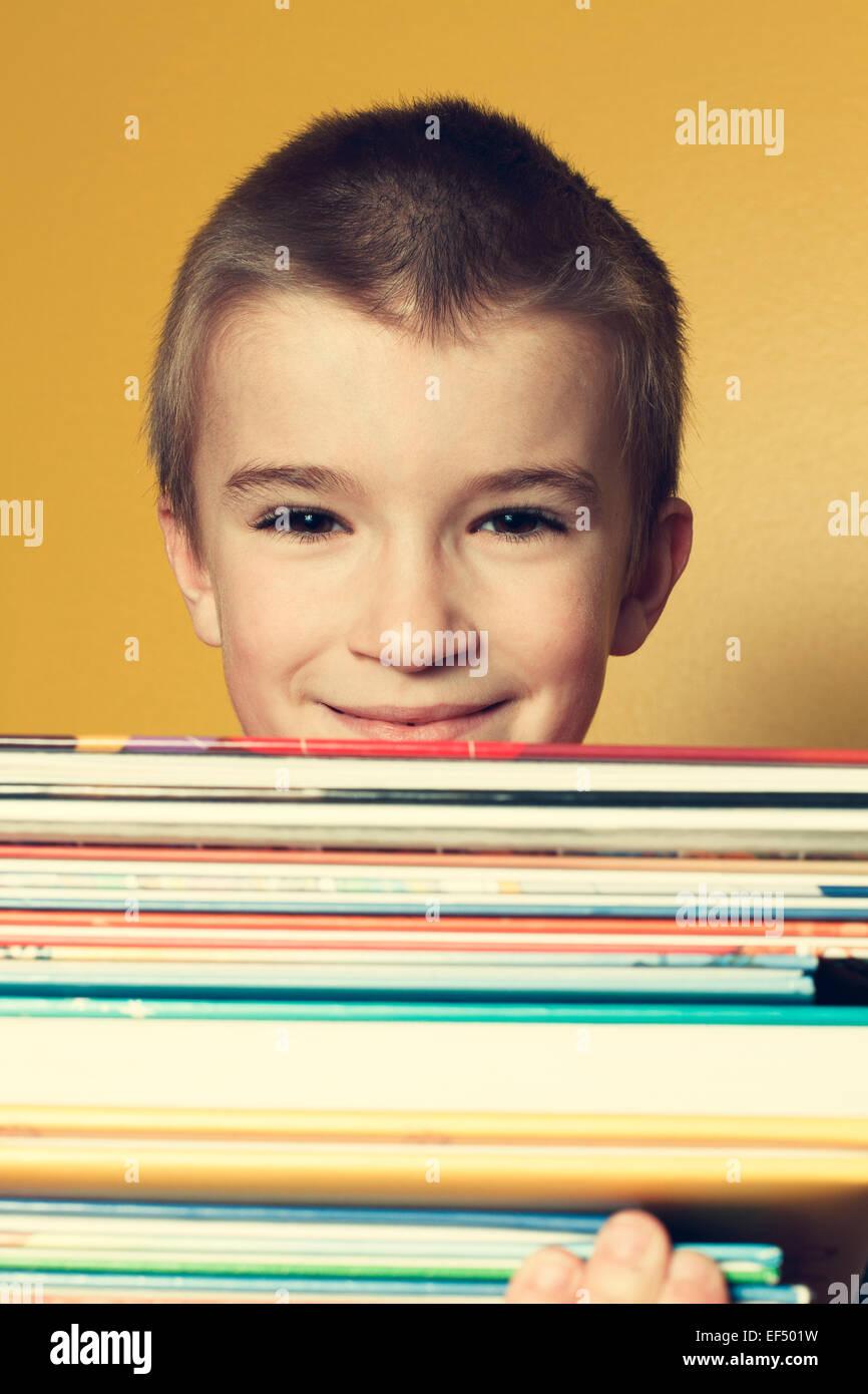 Giovane ragazzo in interni che porta una pila di libri. Foto Stock
