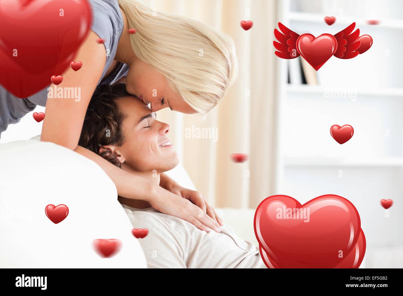 Immagine composita della donna baciare il suo fidanzato sulla fronte Immagini Stock