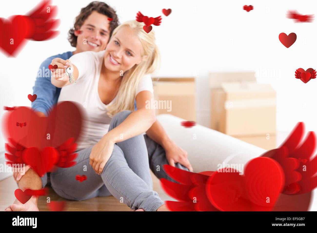 Immagine composita della donna seduta con il suo fidanzato che dà le chiavi Immagini Stock
