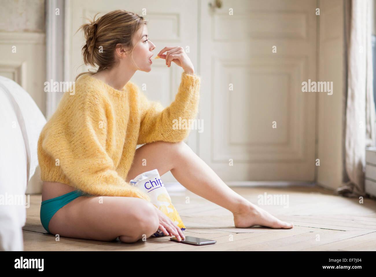 Donna che utilizza il telefono e mangiare patatine Immagini Stock