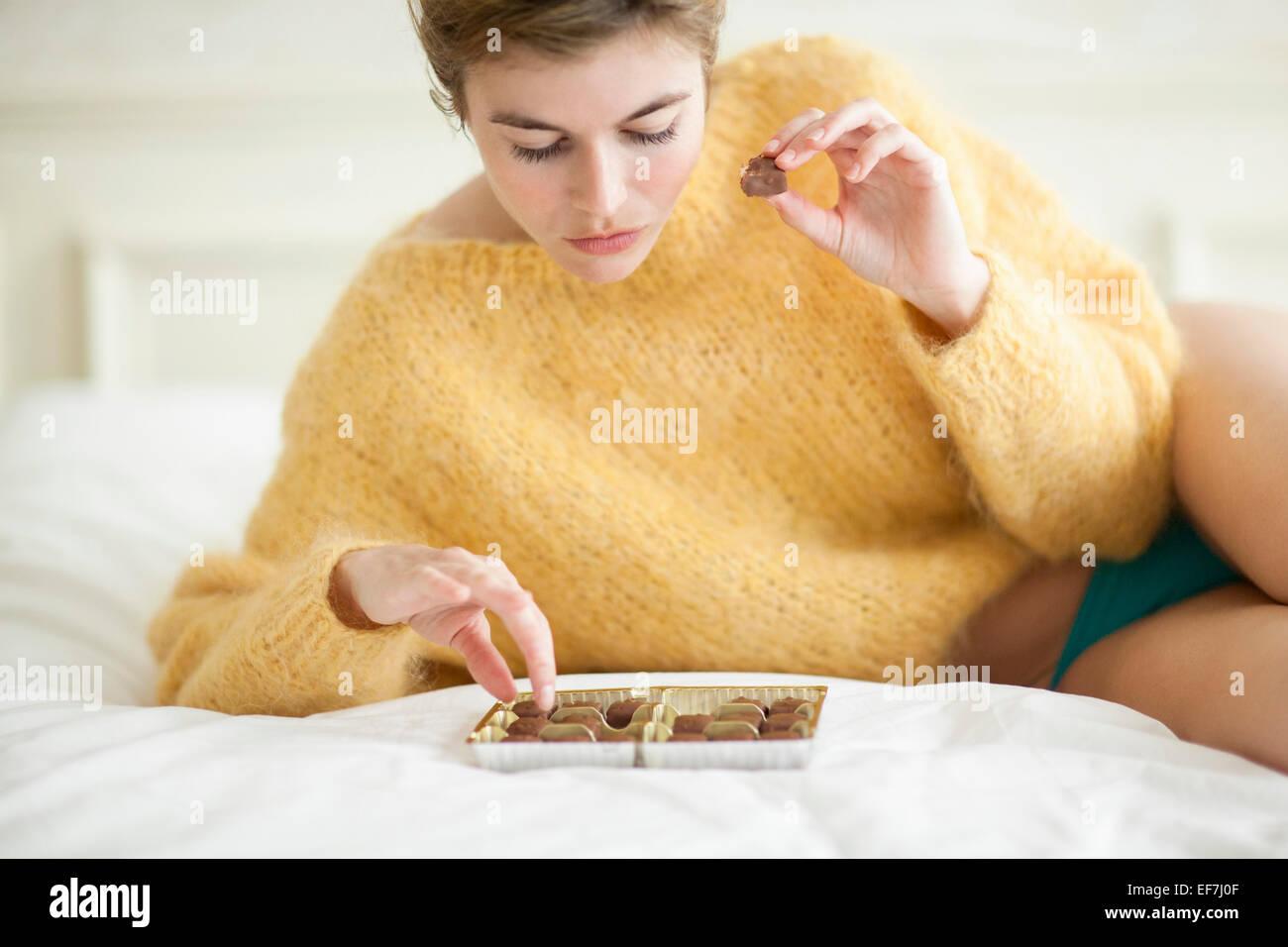Donna mangiare il cioccolato sul letto Immagini Stock