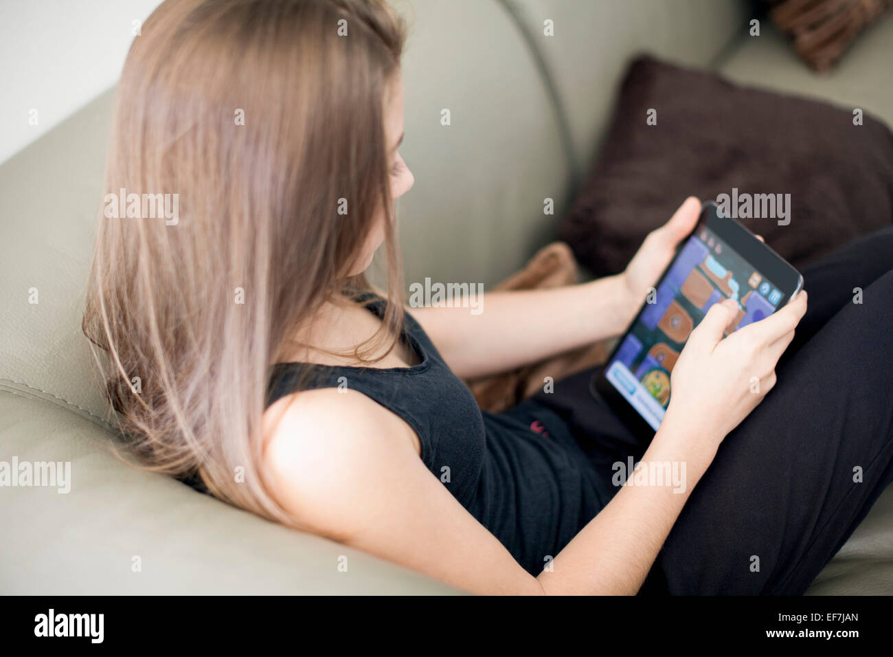 Ragazza adolescente utilizzando digitale compressa sul lettino Immagini Stock