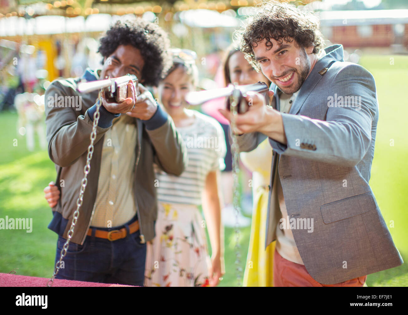 Giovani uomini mirando con armi da fuoco nel parco di divertimenti Immagini Stock