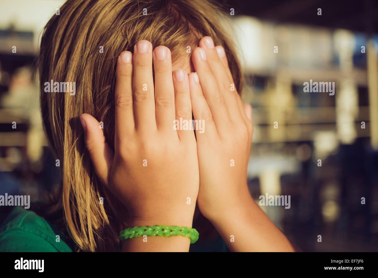 Ragazzo nasconde il viso con le mani Immagini Stock