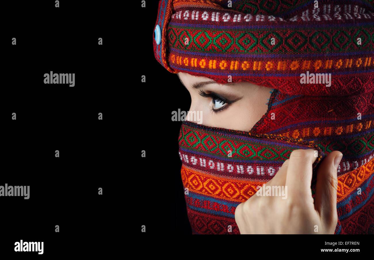 Donna orientale in turbante che copre il volto su sfondo nero Immagini Stock
