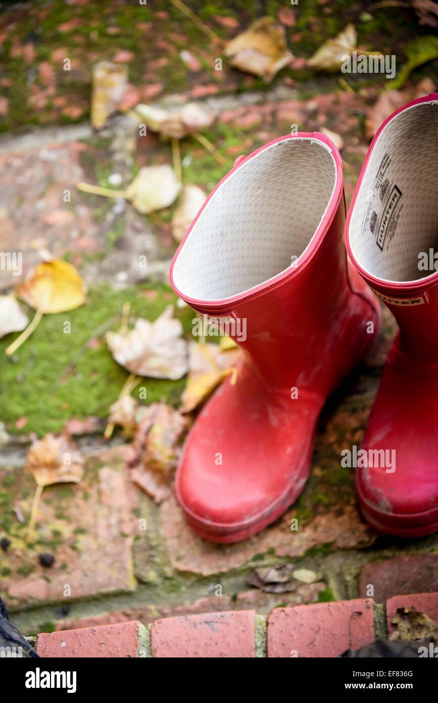 Una coppia di rosso Hunter stivali da pioggia su una porta circondata da foglie. Immagini Stock