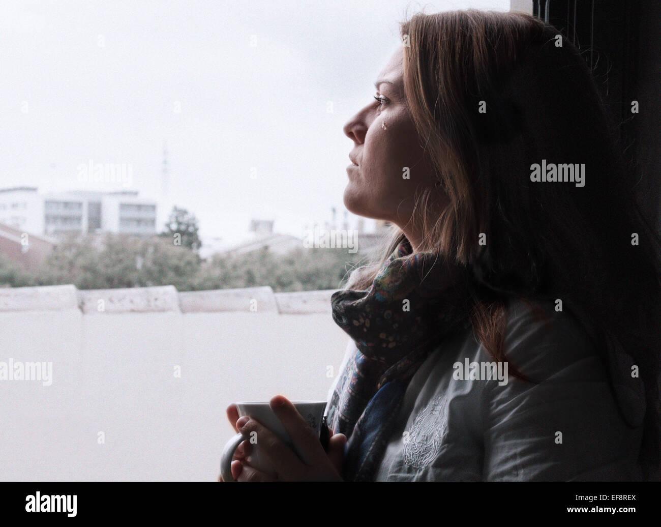 Il pianto donna che guarda attraverso la finestra Immagini Stock
