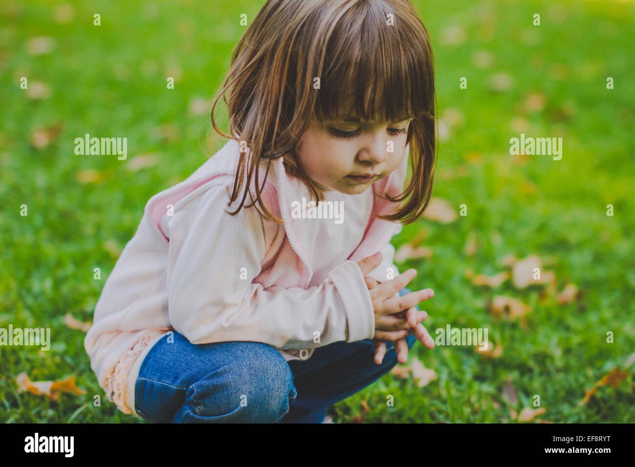 Ritratto di ragazza (2-3) accovacciato sull'erba Immagini Stock