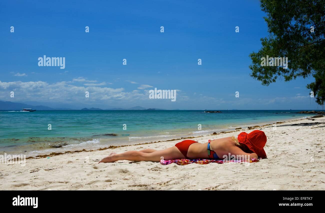 La donna a prendere il sole sulla spiaggia, Malaysia Immagini Stock