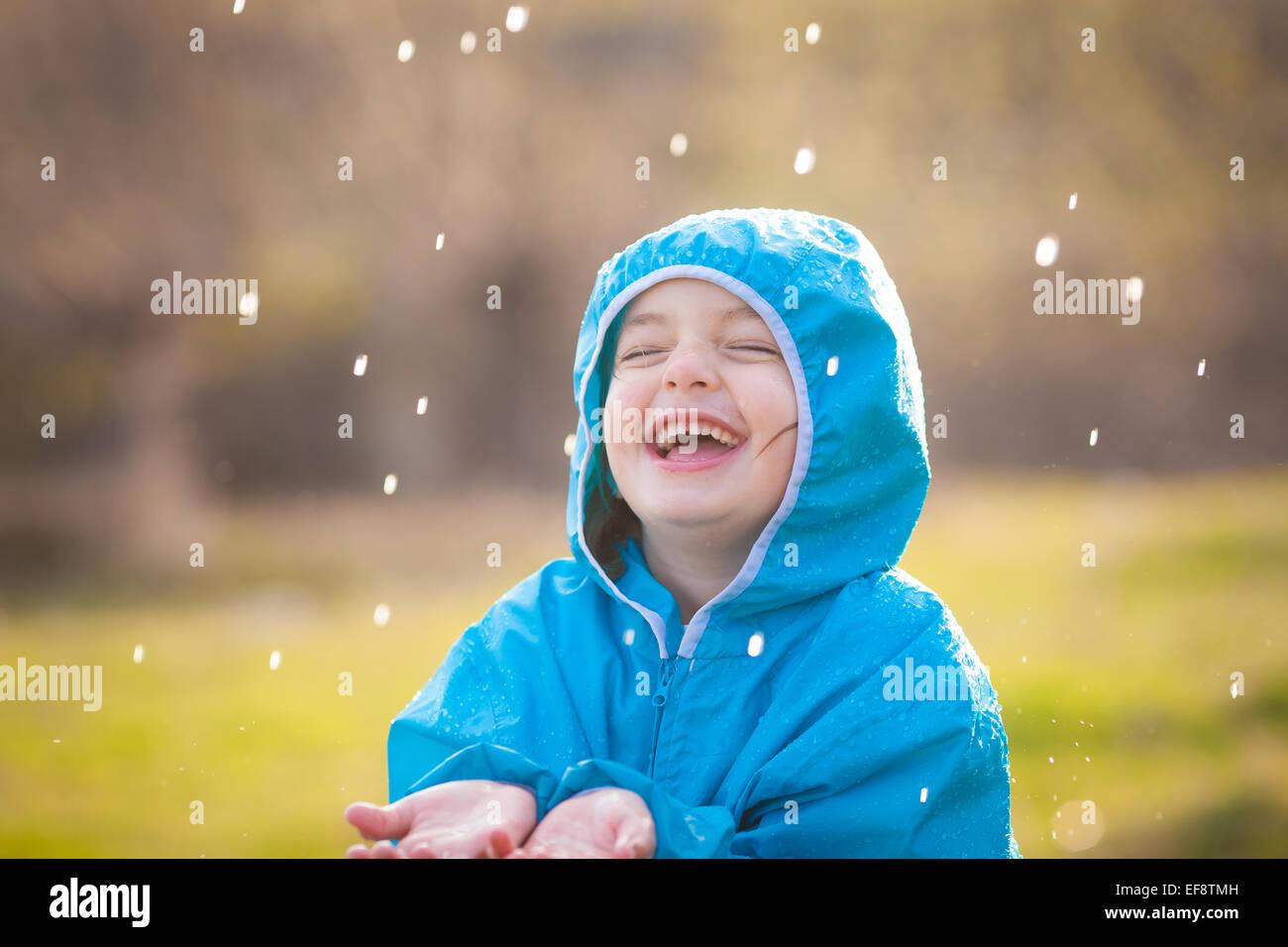 La ragazza (4-5) godendo di pioggia Immagini Stock