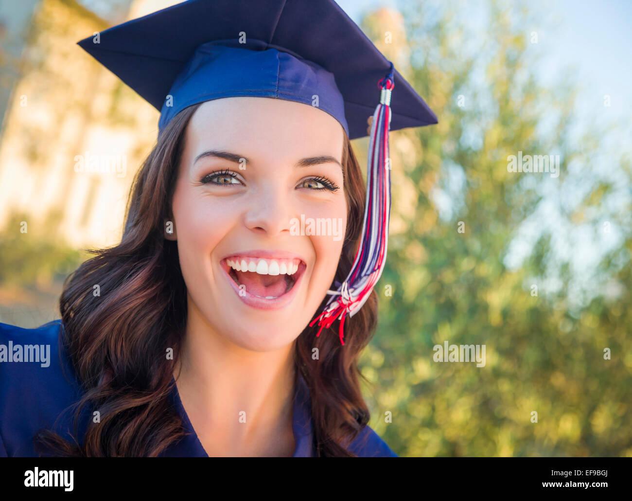 Felice la laurea razza mista donna nel cappuccio e camice celebrando in campus. Immagini Stock