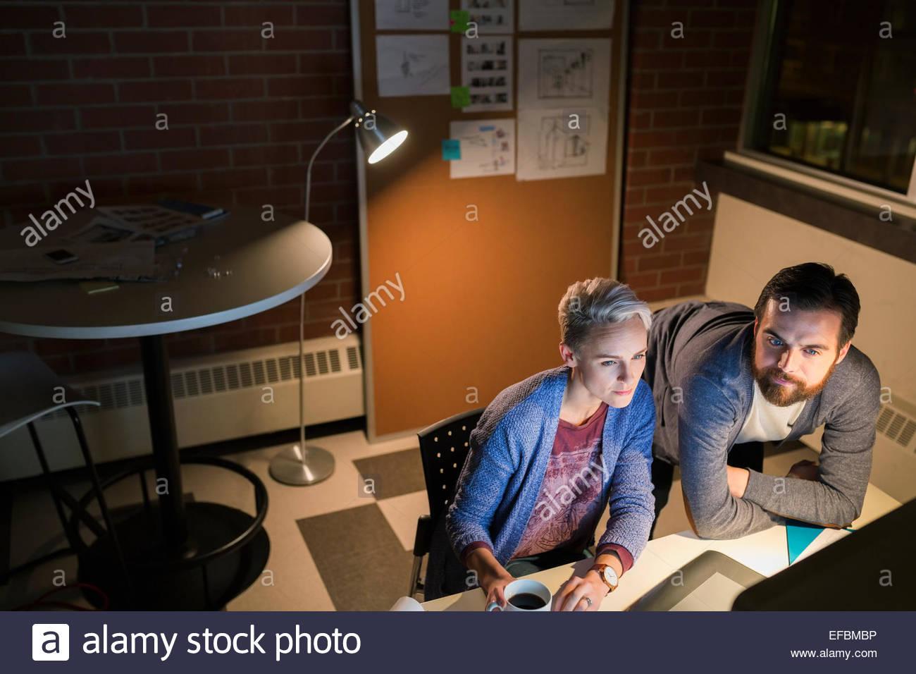 Graphic Designer lavora fino a tardi al computer in ufficio Immagini Stock